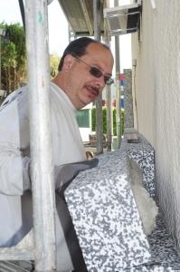 Maler-Engel Patrick Seydler beim Kleben von Dämmplatten
